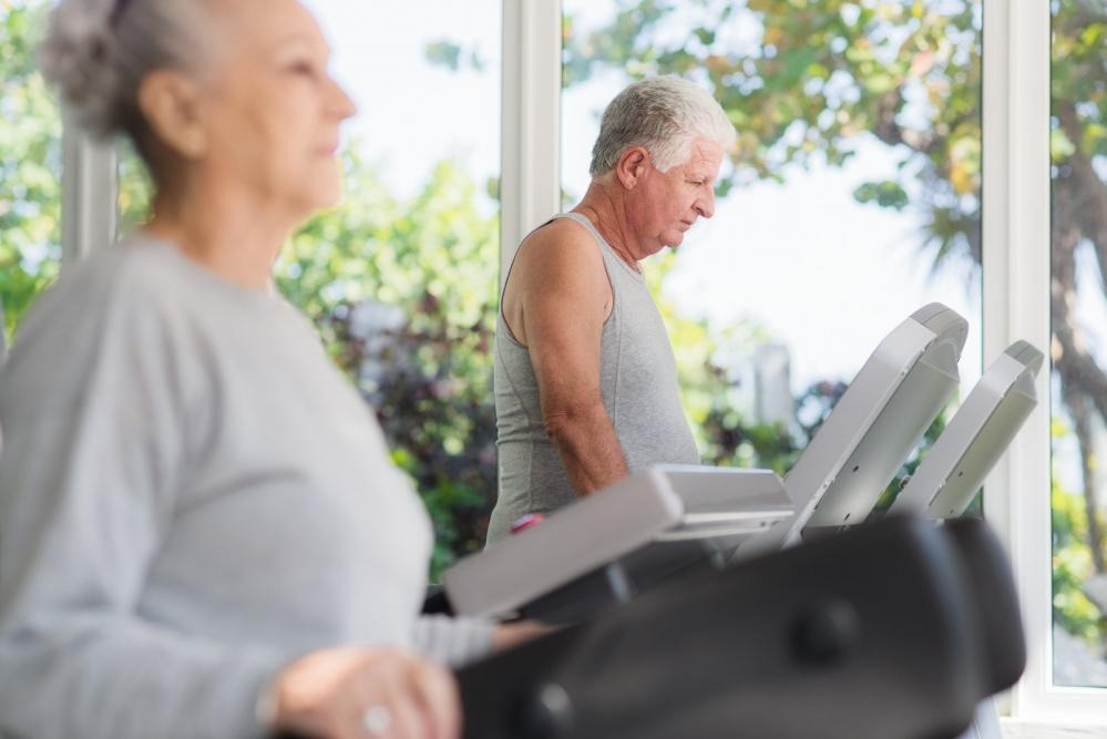 Elderly man and woman on treadmills.